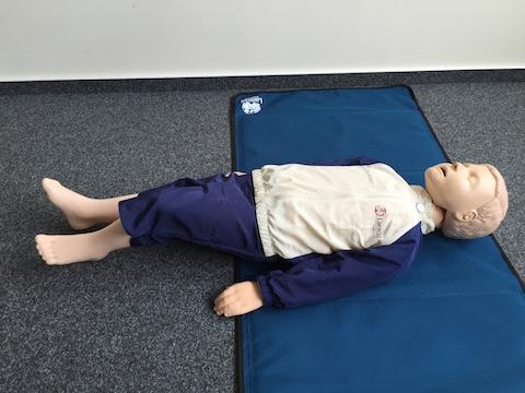 Kind liegt auf dem Boden