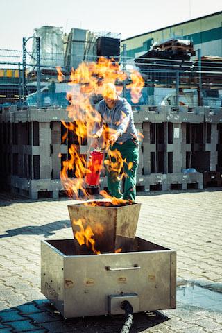Person löscht ein Feuer mit dem Feuerlöscher.